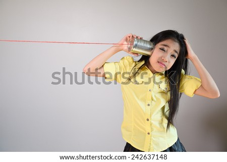 little girl using a can as telephone on a gray background. - stock photo