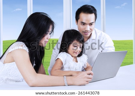 Little girl using a laptop computer on the table with her parents, shot at home - stock photo