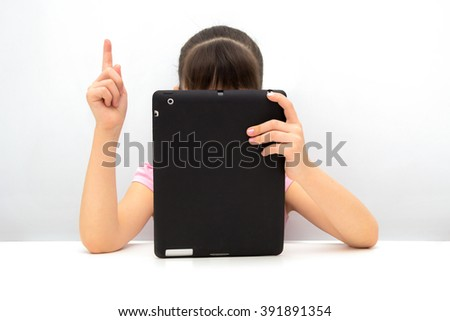 Little girl using a tablet pc - stock photo