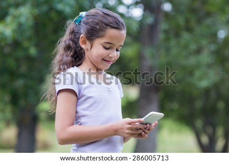 Little girl using her phone on a sunny day