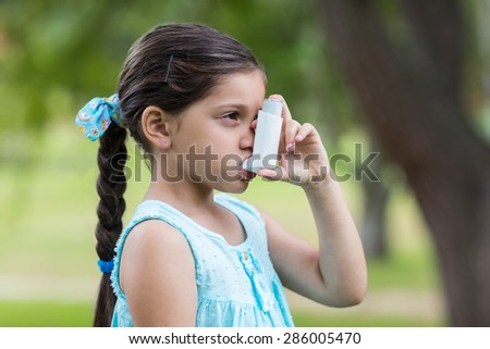 Little girl using his inhaler on a sunny day - stock photo