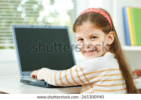 Little girl using laptop computer - stock photo