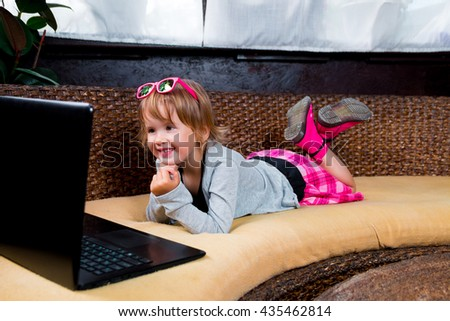 Little girl using laptop. Happy child in pink skirt and pink boots, pink sunglasses, grey top lying at the sofa, playing laptop.  Looking at the screen.