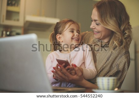 Little girl using smart phone with her mother in the kitchen.