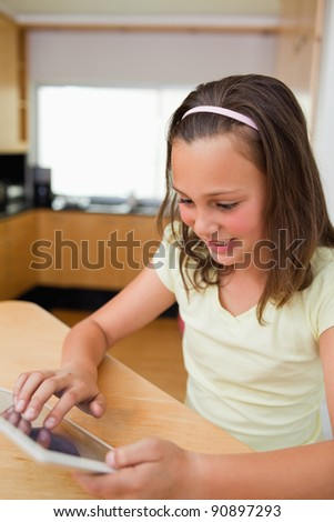 Little girl using tablet at the kitchen table