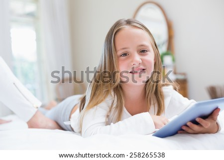 Little girl using tablet pc in the bed at home in the bedroom - stock photo