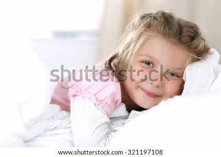 Little girl wake up early morning after sleeping in her bed. Smiling blonde female child awakening portrait in bedroom. Sweet dreams  and good morning concept - stock photo