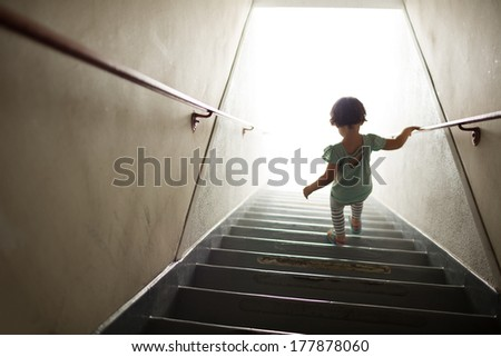 Little girl walking down stairs into white - stock photo