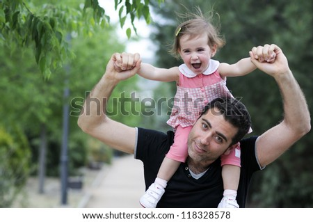 Little girl walking on the shoulders of her father in the park