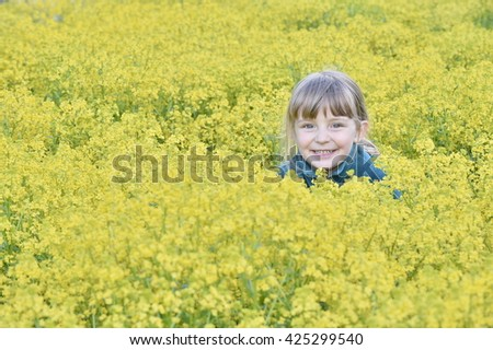 Little girl walking outdoors in the summer meadow with yellow flowers (Barbarea vulgaris, Winter Cress, Common Winter-cress, Yellow Rocket, Herb Barbara, Yellow Rocketcress,   - stock photo