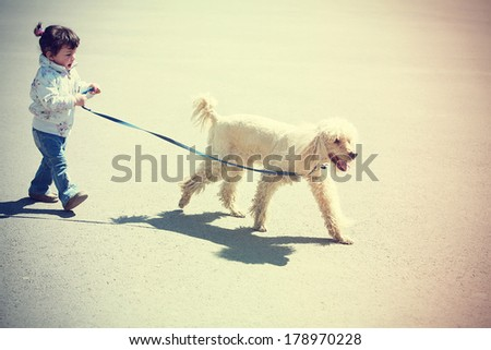 Little girl walking with dog  - stock photo