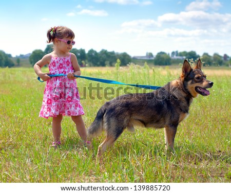 Little girl walking with dog at the meadow and keeping the dog on leash - stock photo