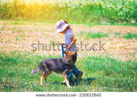 Little girl walking with dog at the meadow and keeping the dog on leash \
