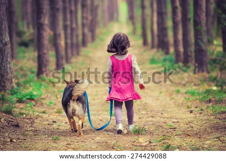 Little girl walking with dog in the forest back to camera - stock photo