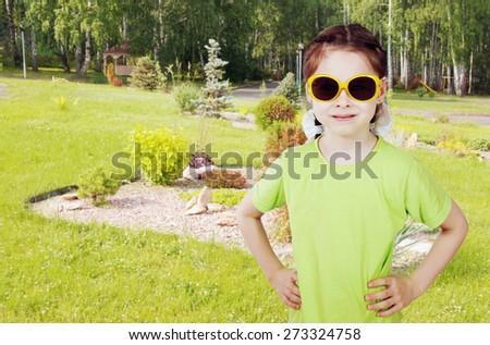 Little girl walks in the summer garden - stock photo