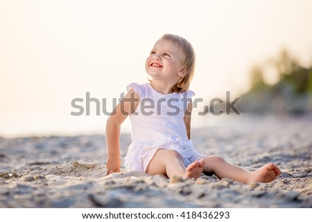 little girl walks on the beach in the summer at sunset