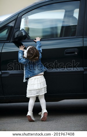 little girl wants to open the car - stock photo