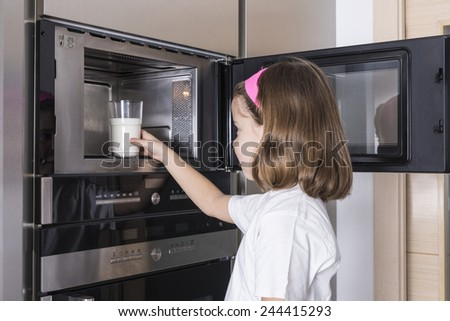 Little girl warming a glass of milk in the microwave