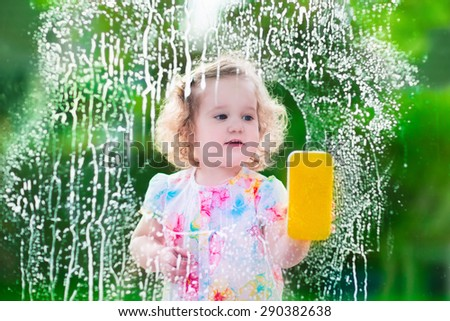Little girl washing a window. Kids clean the house. Children help at home. Toddler kid cleaning windows and doors standing on a ladder. Child helping with housework holding sponge and soap bottle.  - stock photo