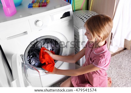 Little girl washing clothes in the machine