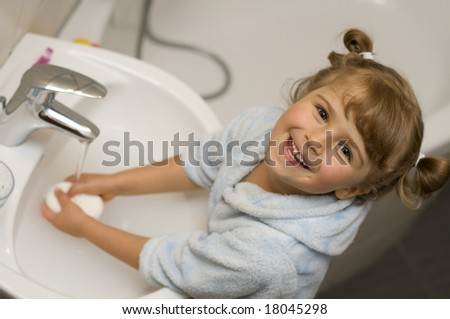 Little girl washing hands in bathroom - stock photo