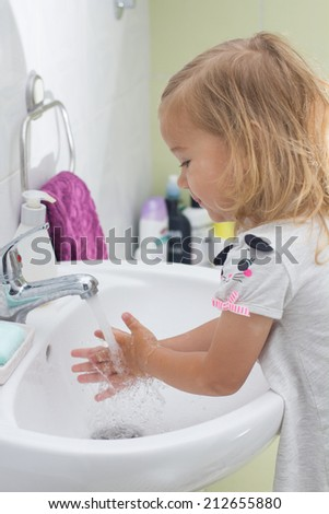 Little girl washing her hands in bathroom. - stock photo