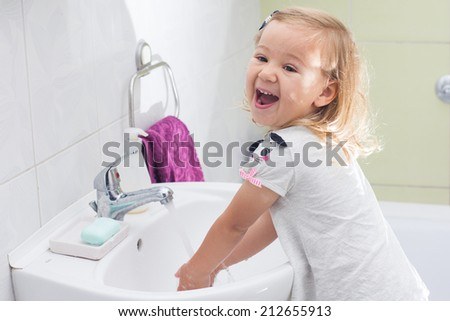 Little girl washing her hands in bathroom.