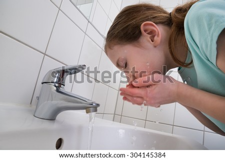 Little Girl Washing Mouth With Water In Bathroom - stock photo