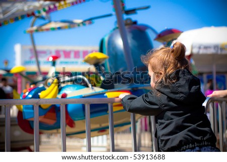 Little girl watches carnival ride - stock photo