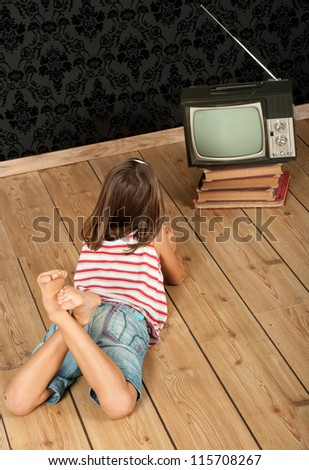 little girl watching old retro tv