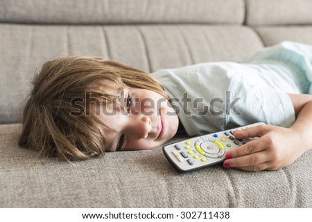 Little girl watching TV on the couch stretched - stock photo
