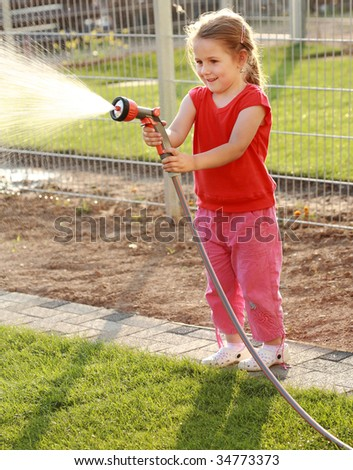 Little girl watering the grass in the garden - stock photo