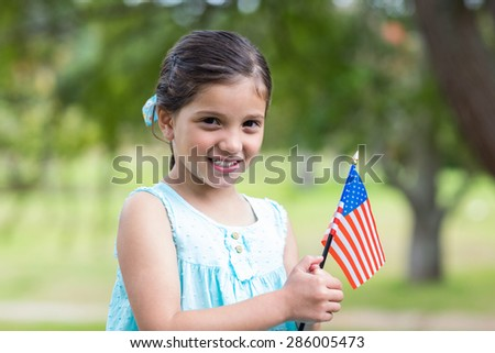 Little girl waving american flag on a sunny day