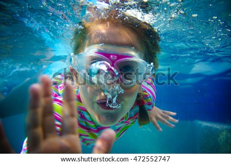 Little girl waving under the water in a swimming pool