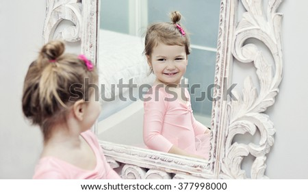 Little girl wearing a ballet tutu getting ready for her ballet lesson - stock photo
