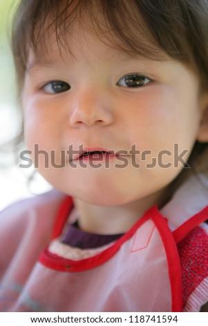 Little girl wearing a bib - stock photo