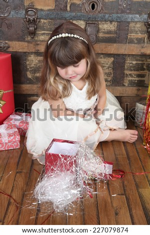 Little girl wearing a christmas dress looking at gifts  - stock photo