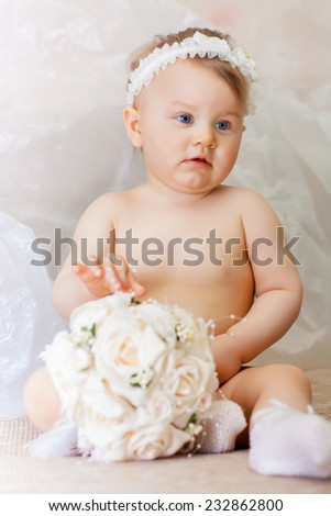 Little girl wearing a crown and with a wedding bouquet - stock photo