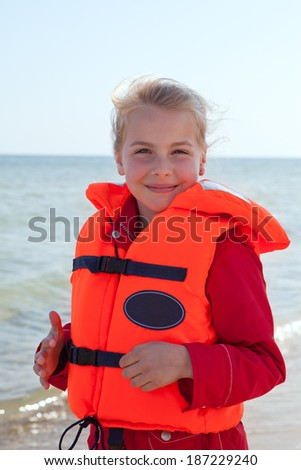 little girl wearing a life jacket at the beach - stock photo