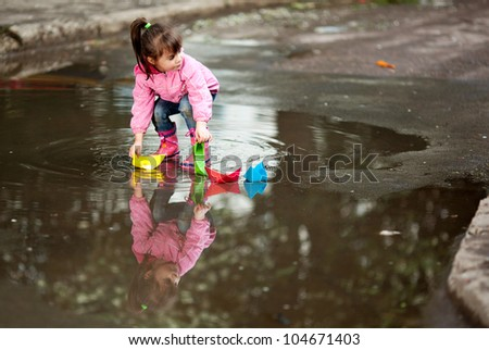 little girl, wearing a pink jacket, playing with colorful paper ship, in the puddle