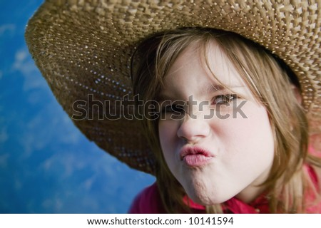 Little girl wearing a straw cowboy hat makes a funny face - stock photo