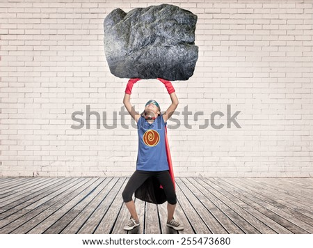 little girl wearing a superhero costume holding a heavy rock - stock photo