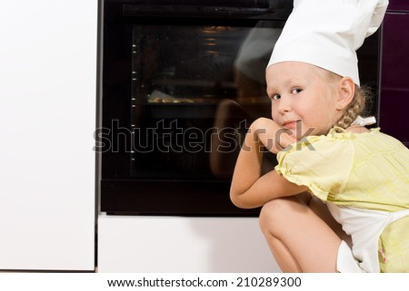 Little girl wearing a white chefs hat and apron crouching down watching her homemade pizza cook in the oven turning to smile over her shoulder - stock photo