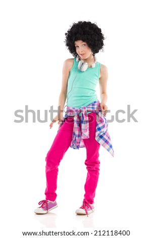 Little girl wearing afro wig and posing with headphones on her neck. Full length studio shot isolated on white. - stock photo