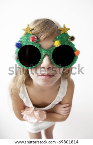 Little girl wearing big round glasses and making a silly expression - stock photo