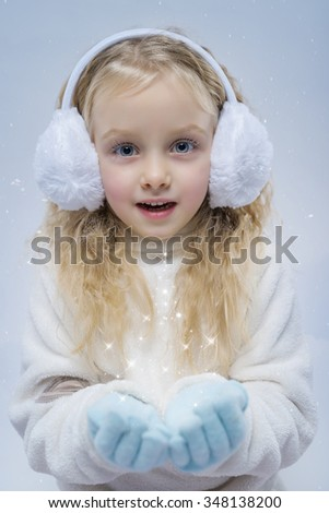 Little girl wearing earmuffs have magic in hands