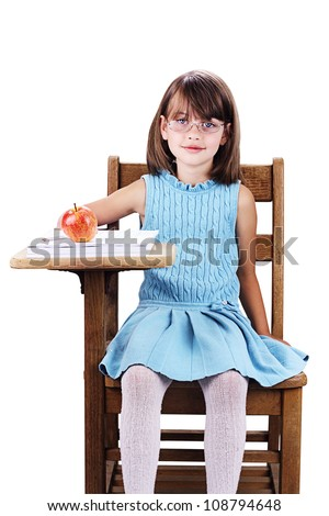 Little girl wearing glasses sitting at a school desk with apple and books. Isolated on a white background with clipping path included.