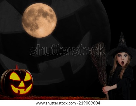 Little girl wearing halloween costume with pumpkin on dark background - stock photo