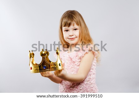 Little girl wearing pink dress and holding metal golden crown, looking at camera, gray studio background, copy space, portrait. - stock photo