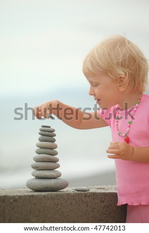 little girl wearing pink dress is building a construction from pebble stones. - stock photo